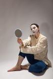 小丑坐与一个镜子的地面在他的手上 图库摄影