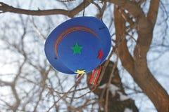 小丑有垂悬在树分支的五颜六色的星的` s呢帽  免版税库存图片