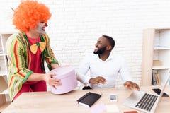 小丑衣服的一个人在他的手上拿着一个箱子以惊奇 免版税库存图片