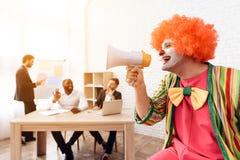 小丑衣服的一个人讲话入扩音器 图库摄影