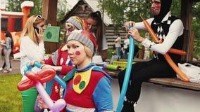 小丑衣服的女孩,与被绘的面孔由气球做图 夏天Fest 股票录像
