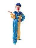 小丑衣服的小男孩与盖帽和一个红色鼻子显示某事用手 免版税库存图片