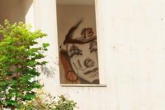 小丑面孔在他的前额的得出的第13在一个被放弃的房子的窗口里 免版税库存照片