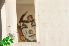 小丑面孔在他的前额的得出的第13在一个被放弃的房子的窗口里 库存图片