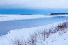 小丘和浮冰在冬天河 免版税库存图片