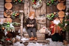 小两岁的男孩在braun皮夹克、裤子和起动穿戴了与试验帽子在摆在圣诞节装饰 图库摄影