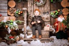 小两岁的男孩在braun皮夹克、裤子和起动穿戴了与试验帽子在摆在圣诞节装饰 库存照片