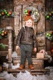 小两岁的男孩在braun皮夹克、裤子和起动穿戴了与试验帽子在摆在圣诞节装饰 库存图片