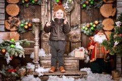 小两岁的男孩在braun皮夹克、裤子和起动穿戴了与试验帽子在摆在圣诞节装饰 免版税库存图片