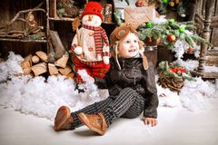小两岁的男孩在braun皮夹克,裤子穿戴了,并且与试验帽子的起动在摆在使用与在圣诞节的雪求爱 免版税库存照片