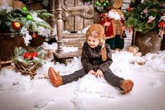 小两岁的男孩在braun皮夹克,裤子穿戴了,并且与试验帽子的起动在摆在使用与在圣诞节的雪求爱 免版税图库摄影