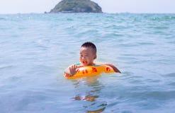 小中国男孩在与橡胶环的海湾游泳在背景海岛 免版税图库摄影