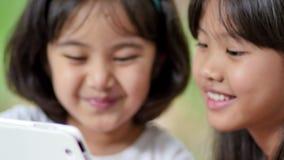 小亚裔儿童观看的片剂在公园一起 股票录像