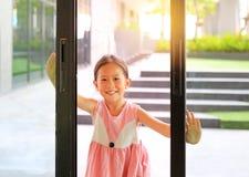 小亚裔在客厅前面的儿童开放玻璃门 免版税库存图片