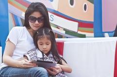 小亚裔女孩和妈妈享用片剂个人计算机。 免版税库存照片