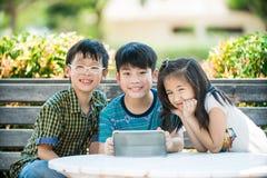 小亚裔女孩和男孩坐长的木椅子使用数字 免版税库存照片