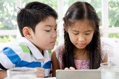 小亚裔女孩和男孩有片剂计算机的 免版税库存图片