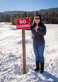 小亚裔女孩显示哀伤的面孔没有sledding标志 免版税图库摄影