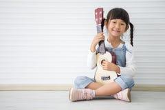 小亚裔女孩演奏尤克里里琴坐与拷贝空间的白色背景 免版税库存照片