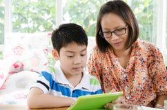 小亚裔母亲和儿子有片剂计算机的 免版税库存照片