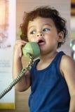 小亚裔男婴谈话在一个减速火箭的电话 库存图片