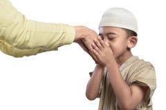 小亚洲回教孩子在白色盖帽亲吻的父母手上 图库摄影