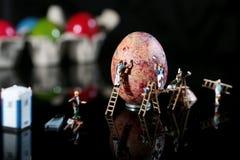 小人用一个大鸡蛋 图库摄影