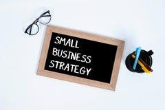 小企业/概念性 小企业在黑板写的战略文本顶视图为与玻璃的事务,标志和 免版税库存照片