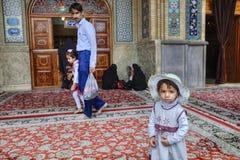 小伊朗女孩佩带的海滩盖帽在清真寺庭院里站立 免版税图库摄影