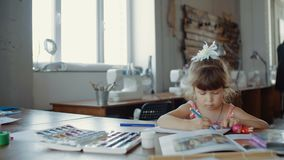 小俏丽的女孩画与色的标志在桌上在屋子里 影视素材