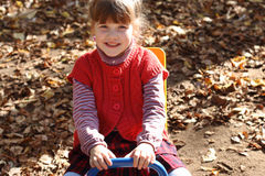 小俏丽的微笑的女孩坐木跷跷板 库存图片