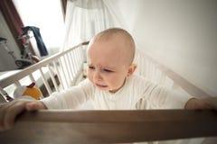 小儿床哭泣的被抛弃的婴孩 库存照片