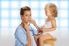 小儿科有听诊器的检查小女孩 免版税库存照片