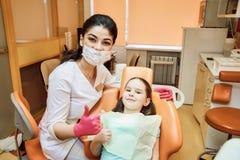 小儿科牙科 牙医和女孩看看照相机和微笑 图库摄影