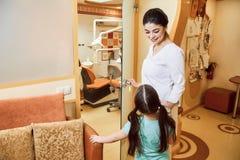 小儿科牙科 牙医邀请女孩到办公室 免版税库存图片