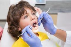 小儿科牙医审查在牙医椅子的小男孩牙 库存照片