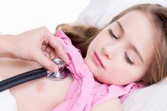 小儿科医生审查有听诊器的小女孩。 库存图片