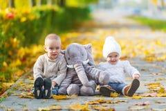 小兄弟和姐妹获得乐趣在秋天公园 库存图片
