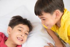 小兄弟姐妹男孩在地板上的枕头一起放置 图库摄影