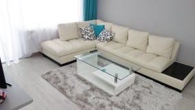 小公寓客厅设计想法,皮革长沙发,化装室,咖啡桌,灰色豪华地毯,现代木条地板纹理, t 免版税库存照片