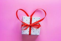 小典雅的礼物盒栓与与弓的红色丝带在桃红色背景的心脏形状 华伦泰贺卡婚礼 免版税库存图片