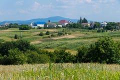 小农村房子多彩多姿的屋顶以绿色迷雾山脉为背景的在距离 免版税库存图片