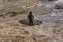 小冲浪者女孩在Ribeira de Ilhas Beach在Ericeira葡萄牙 免版税库存图片