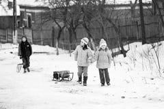 小南部的罗马尼亚村庄 场面从与使用与爬犁和享用雪的孩子的一个喜怒无常的冬天 库存照片