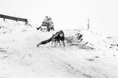 小南部的罗马尼亚村庄 场面从与使用与爬犁和享用雪的孩子的一个喜怒无常的冬天 库存图片