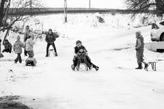 小南部的罗马尼亚村庄 场面从与使用与爬犁和享用雪的孩子的一个喜怒无常的冬天 图库摄影