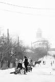 小南部的罗马尼亚村庄 场面从与使用与爬犁和享用雪的孩子的一个喜怒无常的冬天 免版税库存照片