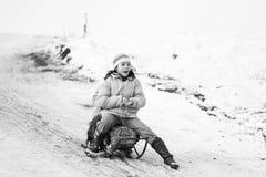 小南部的罗马尼亚村庄 场面从与使用与爬犁和享用雪的孩子的一个喜怒无常的冬天 免版税库存图片