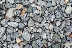 小卵石向背景扔石头 库存图片
