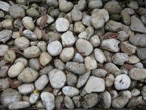 小卵石向背景扔石头 免版税图库摄影
